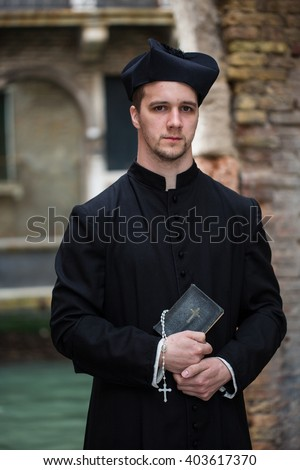 young priest in venice in front of canal - stock photo