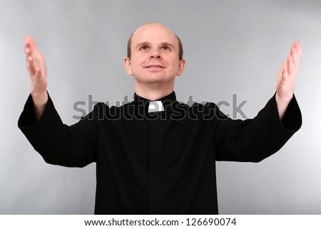 Young priest on gray background - stock photo