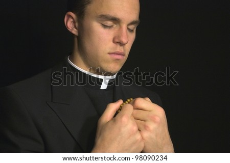 Young Priest praying - stock photo