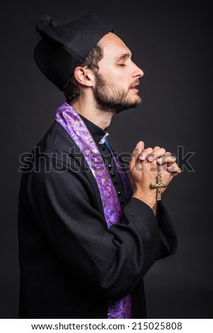 Young priest praying. Studio portrait on black background   - stock photo
