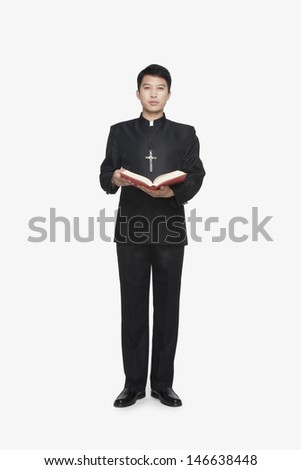 Young Priest Standing with Bible - stock photo