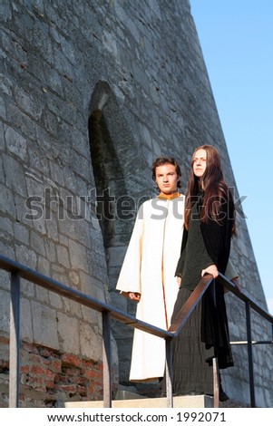 Young prince and princess in a medieval place with castle ruin - stock photo