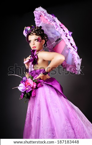Young Princess with flowers in her hat and umbrella - stock photo