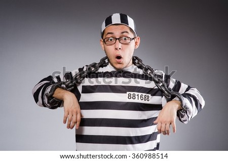 Young prisoner in chains against gray - stock photo