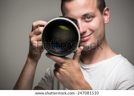 Young pro photographer with digital camera - DSLR and a huge telephoto lens in her well equiped studio, taking photos (color toned image; shallow DOF) - stock photo