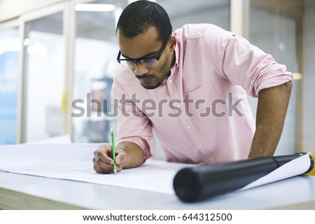 Young professional afro american engineer creating stock photo young professional afro american engineer creating graphic of building exterior on sketch in architectural company indoors malvernweather Gallery