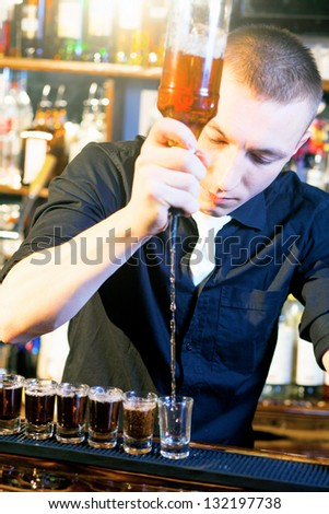 Young professional barman in action making  drink shots - stock photo