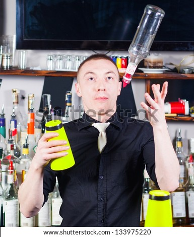 Young professional barman in action with shaker and bottle making cocktail drinks - stock photo