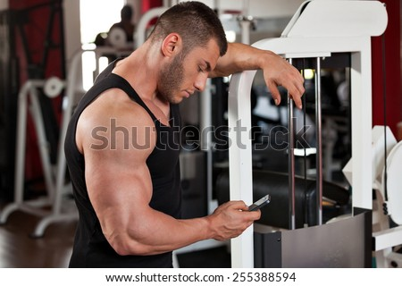 young professional bodybuilder in the gym, in a break, looking at his phone