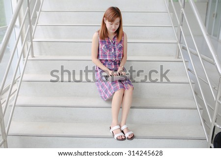 Young professional business woman sitting on the steps of an old stone building using a laptop computer working outdoors - stock photo