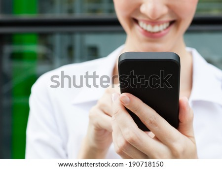 Young professional business woman using mobile smart phone. - stock photo