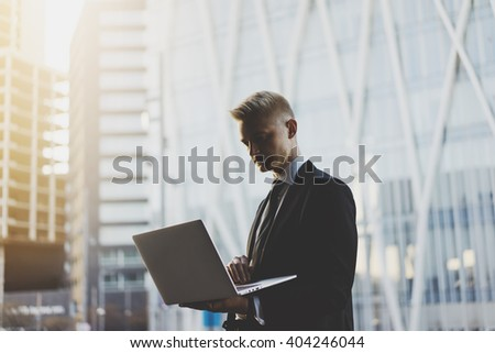 Young professional businessman using laptop outside while working on new project of modern office or living house, flare light - stock photo
