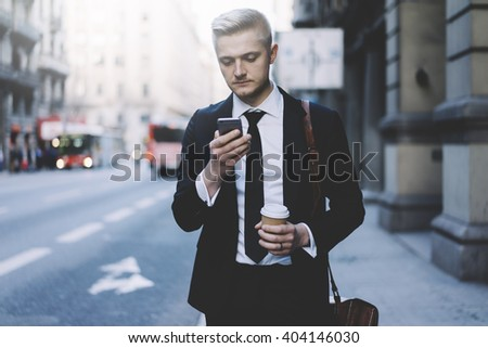 Young professional businessman using modern smartphone outdoors, successful lawyer wearing black suit and using his cellphone while going to the work and take taxi - stock photo