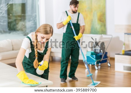 Young professional cleaners cleaning accurate spacious apartment. Man mopping the floor and girl polishing the table - stock photo