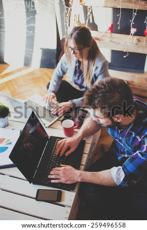 Young professional couple working together - stock photo