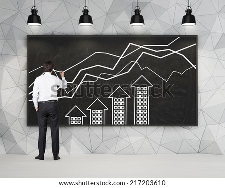 Young professional drawing a growing real estate chart.   - stock photo