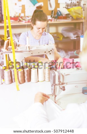 young professional female tailor using sewing machine at workshop