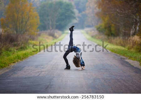 Young professional gymnast makes splits on the road at autumn time - stock photo