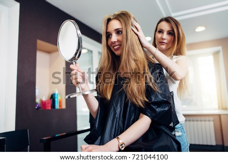 young professional hairstylist finished the haircut and show the result to the customer looking in mirror