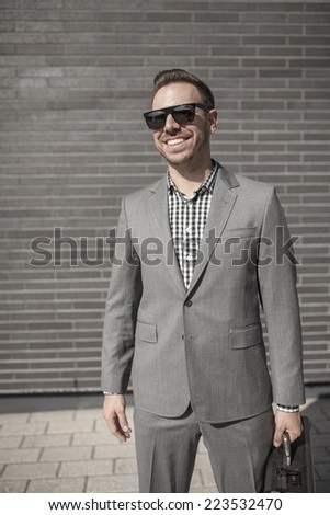 Young professional in business attire projecting confidence against brick wall