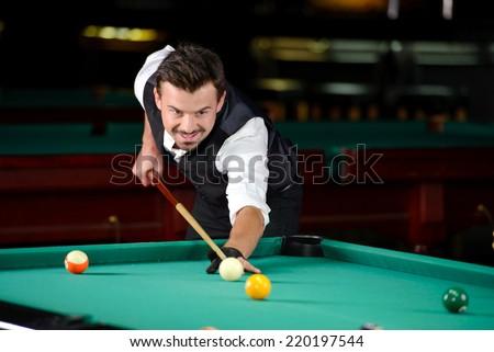 Young professional man playing billiards in the dark billiard club - stock photo