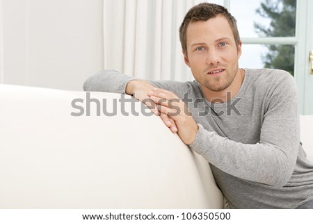 Young professional man sitting on a white sofa at home, smiling. - stock photo