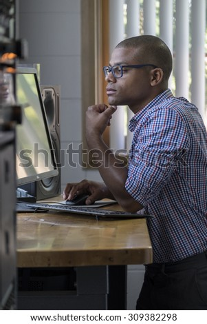 Young professional man standing at his computer desk in the office