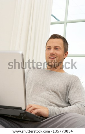 Young professional man using a laptop computer while sitting on a white sofa at home. - stock photo