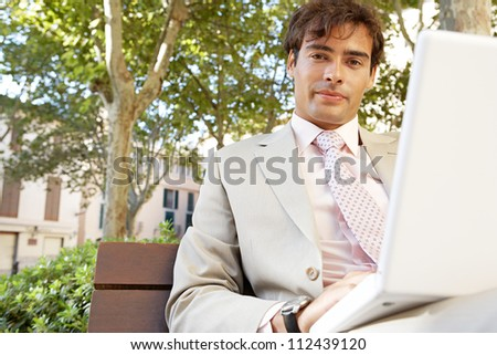 Young professional man using a laptop pc while sitting on a bench in a classic city square. - stock photo