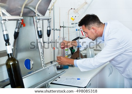 Young professional man working with quality tests at a wine manufactory