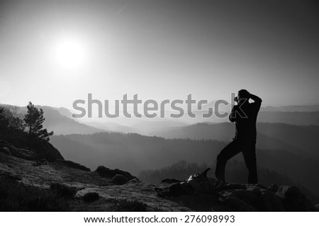 Young professional photographer takes photos with mirror camera on peak of rock. Dreamy fogy landscape. Black and white photo