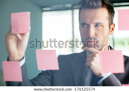 Young professional thinking hard and sticking  notes to a glass wall - stock photo