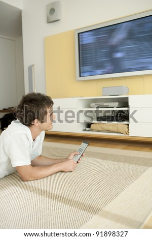Young professional using a tv remote control while watching a flat screen tv at home. - stock photo
