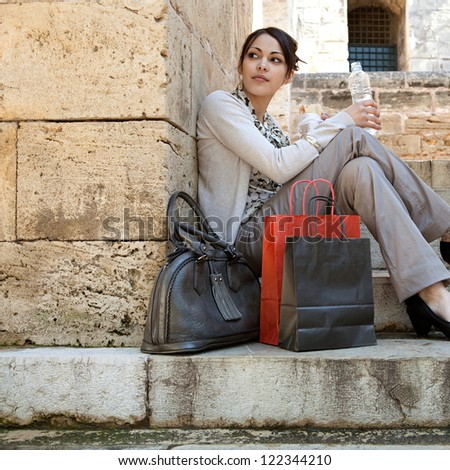 Young professional woman having a lunch break and sitting down on a park steps with her shopping bags and bottle of water.