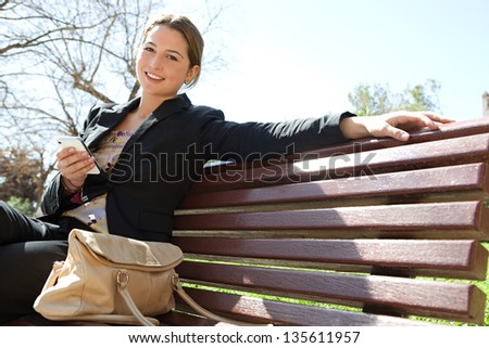 Young professional woman sitting on a wooden bench in a city park, holding her smartphone and smiling at the camera during a sunny day.