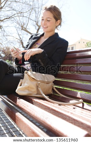 Young professional woman sitting on a wooden bench in a city park, using the touch screen of her smartphone, smiling. - stock photo