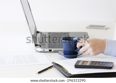 Young professional woman works on financial  reports of a company by using technological tools and equipments.She evaluates the performance and success of the management of divisions in a company. - stock photo