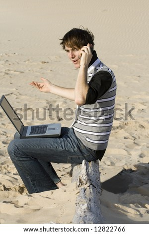 Young professional working on the beach talking to a client - stock photo