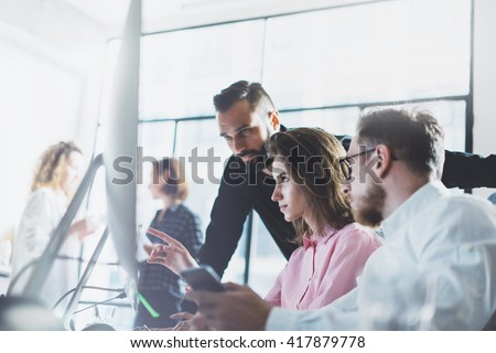 Young professionals work in modern office.Project manager team discussing new idea.Business crew working with startup.Desktop computer table,showing presentation, monitor.Blurred,film effect. - stock photo