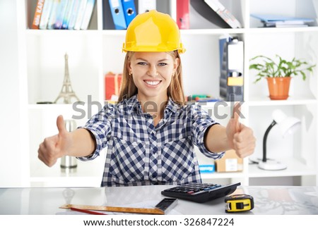Young prosperous woman engineer in hardhat showing thumbs up at her workplace. Attractive female architect measuring blueprint and calculating business plan.   - stock photo