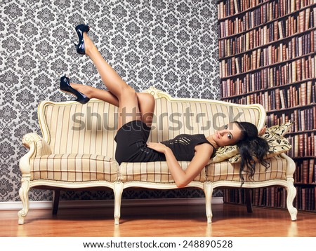 young provocative woman lying on couch, interior  - stock photo