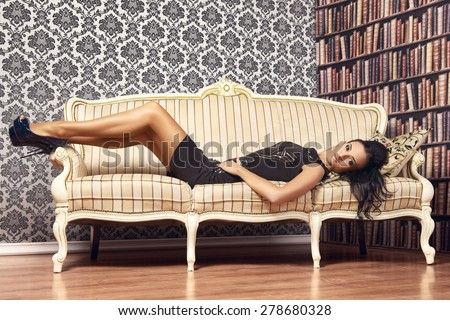 young provocative woman on couch at home - stock photo