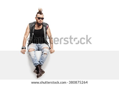 Young punk rocker with a Mohawk hairstyle and a leather vest sitting on a panel isolated on white background - stock photo