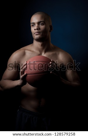 young purposeful black athlete holding basketball ball isolated on gradient blue background - stock photo