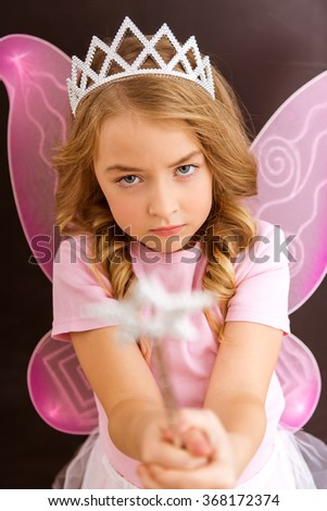 Young queen fairy with pink wings against a dark background holding a magic wand forward