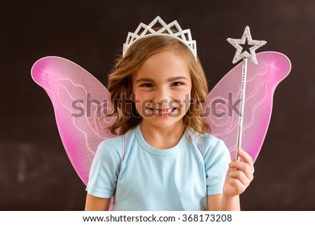Young queen fairy with pink wings holding a magic wand against dark background - stock photo