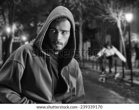 Young rapper on a lonely street at night and in the background a skateboarder - stock photo