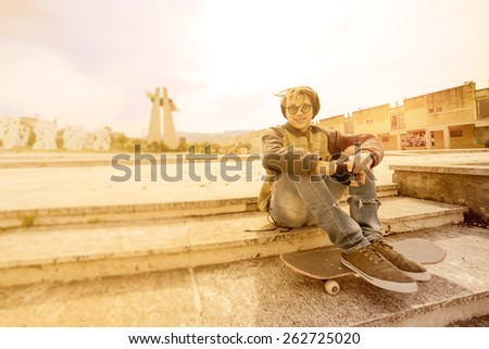 young rasta guy outdoor sitting on his skate with a warm filter applied - stock photo