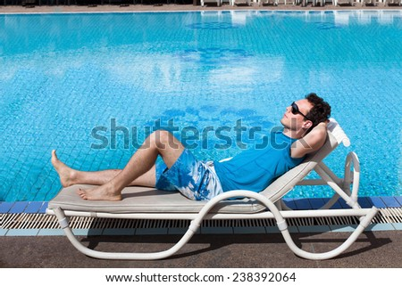 young reach suc?essful businessman relaxing near big luxury swimming pool - stock photo
