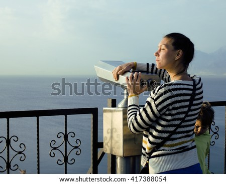 young real woman looking through telescope at sea viewpoint in Ataturk park, sunny morning - stock photo